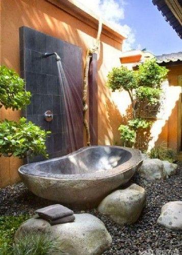 Une douche d'extérieure avec une baignoire en pierres pour receveur  installée…