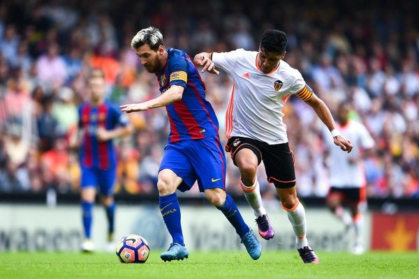 Lionel Messi of FC Barcelona competes for the ball with Enzo Perez of Valencia CF during the La Liga match between Valencia CF and FC Barcelona at Mestalla stadium on October 22, 2016 in Valencia, Spain.