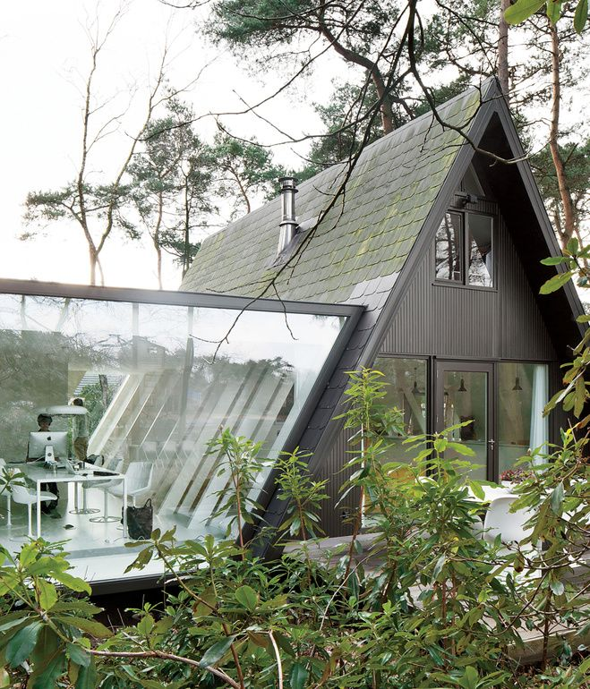 For this tiny house in the forest of Brecht, Belgium, a little extra square footage comes in the form of a glassed-in addition with a stellar view.