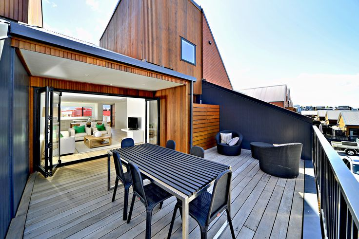 The sharp lines and architectural angles compliment the stained wooden cladding and provide a contemporary out-door seating area, perfect for the modern family