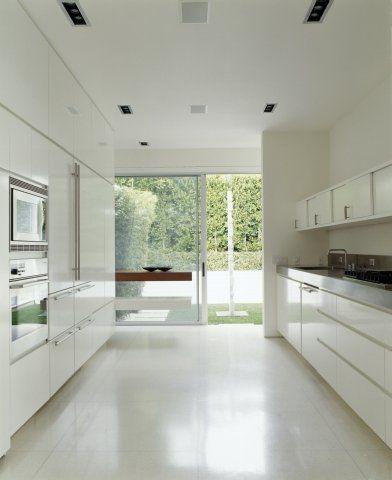 W tej minimalistycznej, białej kuchni nic nie zakłóca widoku na ogród. Układ równoległy szafek tworzy przejście, którego naturalnym przedłużeniem jest zielona przestrzeń na zewnątrz domu.