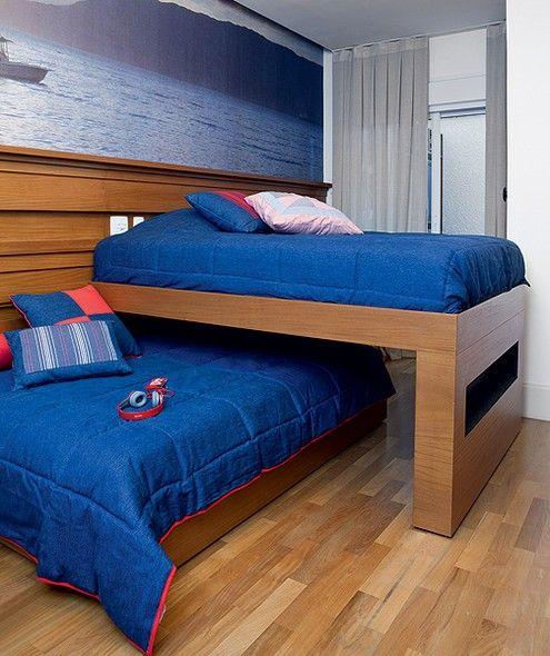 O quarto de irmãos tem duas camas sobrepostas na perpendicular, que correm para lados opostos em rodízios no chão e embutidos em ripado de peroba na parede. Assim, elas só ocupam todo o espaço na hora de dormir. Projeto da arquiteta Fabiana Avanzi