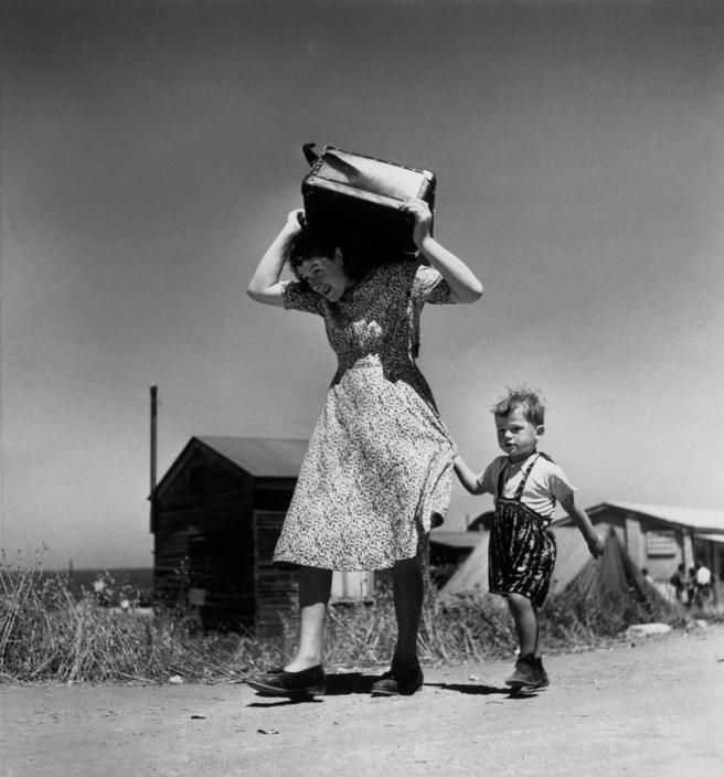 Woman carrying luggage accompanied by a small boy, Haifa, 1949 by Robert Capa