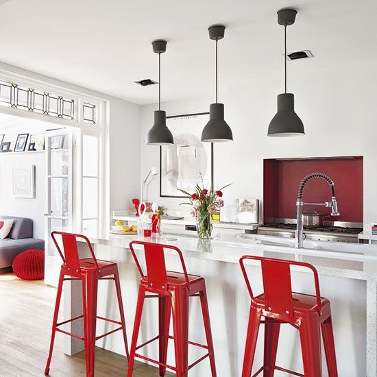 White open-plan kitchen with pendants and stools