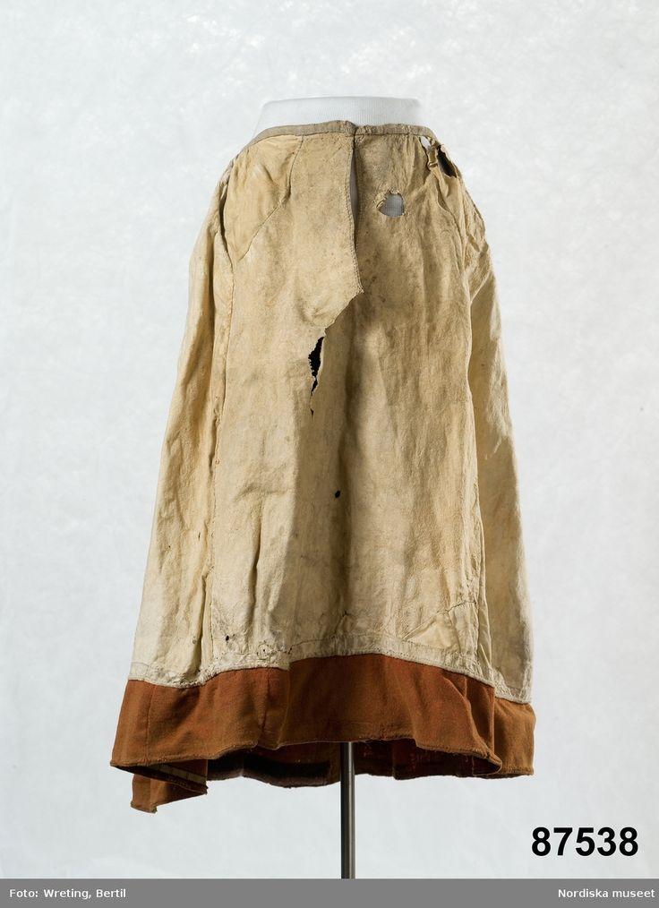 Kjol av ljust gult sämskskinn med en list av rött vadmal i nederkanten. Var vit och röd ursprungligen. SE Öland