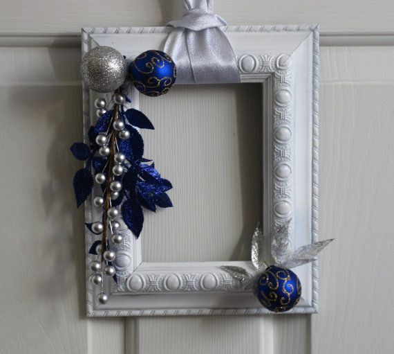 Modern, unique and definitely one-of-a-kind! Be the first person on your block to sport a trendy frame wreath. With some paint, ribbon and the proper holiday embellishments, these picture frames are transformed into festive holiday hangings that elegantly combine a unique shape with favorite holiday decorations.   I gave this frame a white finish and partnered it with silver and deep blue embellishments. The result is a wreath with a Winter Wonderland feel to it. The wreath hangs by the…