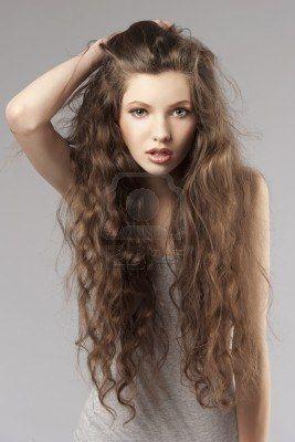 giovane ragazza carina capelli lunghi ricci in un porteait su sfondo grigio Archivio Fotografico