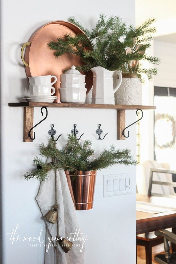 Rustic open shelving in the kitchen, decorated for Christmas with white pottery and greenery. From The Wood Grain Cottage.