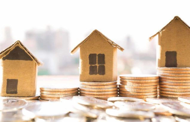 cardboard houses stacked on top of coins housing costs