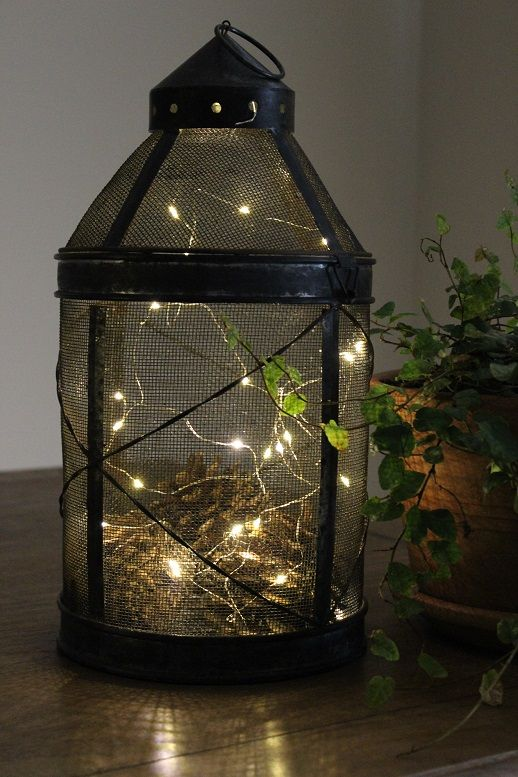 Vintage style tree lantern. Looks old and a bit rusty, like its been hanging in Grandma's garden for years. Filled with wire 'firefly' fairy lights. Enchanting!