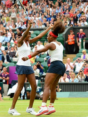 Venus Williams (left) and Serena Williams celebrate after winning match point against Andrea Hlavackova and Lucie Hradeka of the Czech Republic to win the tennis women's doubles gold medal on Sunday at the All England Club.