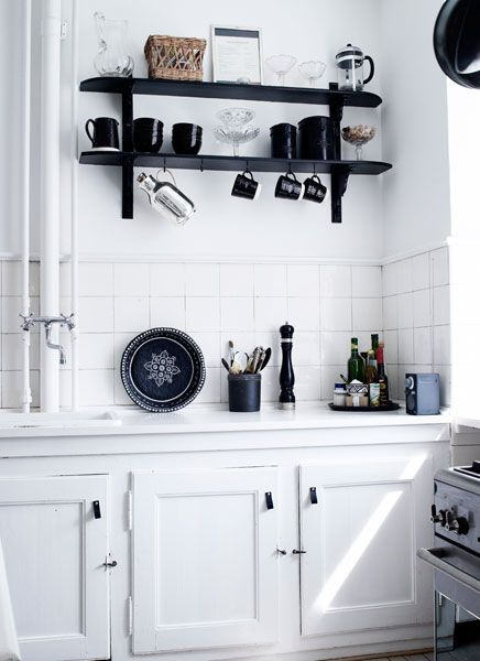 All white kitchen, black contrasting cabinet knobs, small black shelf to add storage (good idea that looks good too!)