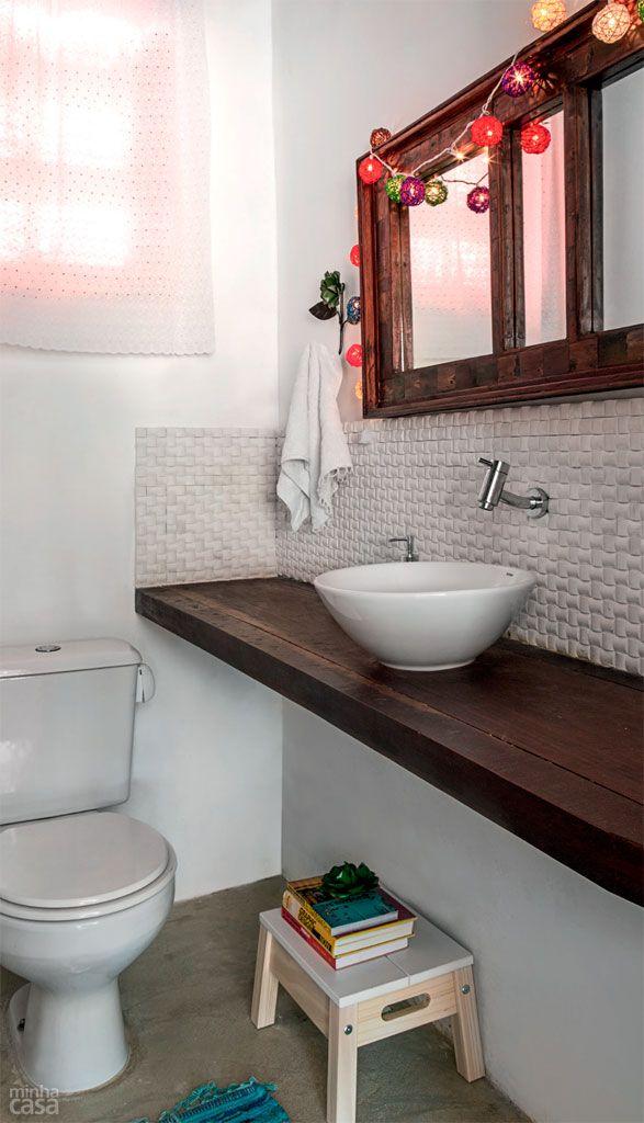 O lavabo simples com pia apoiada em uma bancada de madeira ipê, acompanhada de um revestimento cimentício que exibe acabamento em relevo.