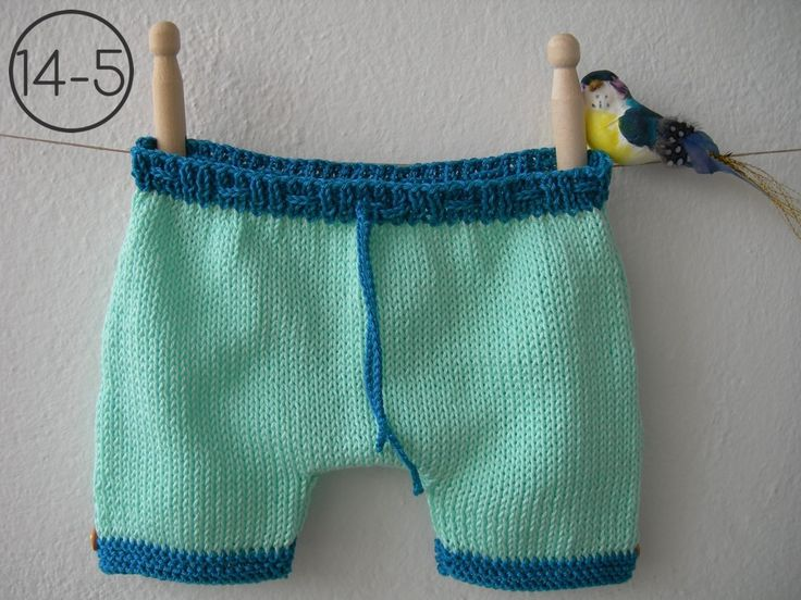 Pantalón en punto jersey de color aguamarina con elásticos en color azul petróleo. El elástico de la cintura lleva un cordón para ajustar y los de las piernas en punto bobo con botón de madera lateral.
