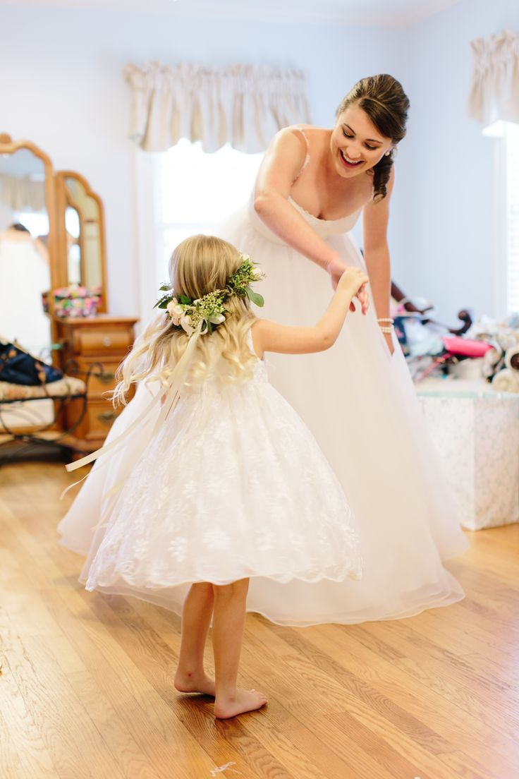 the bride and flower girl in her rose and eucalyptus halo share a moment of twirling in their wedding day dresses.