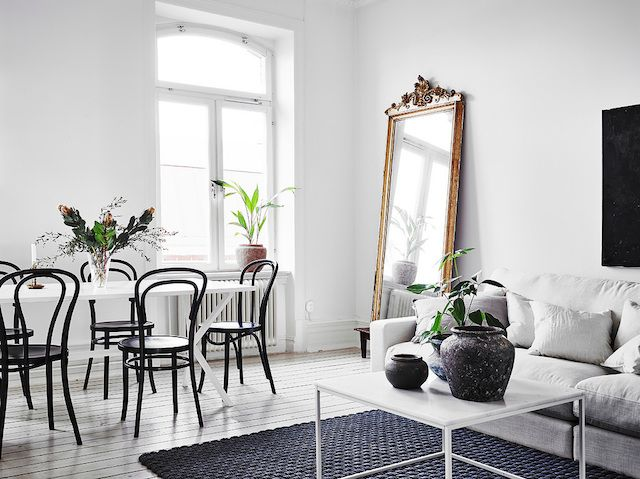 Gilt-framed mirror in an open plan sitting room / dining area in a magnificent white Swedish apartment