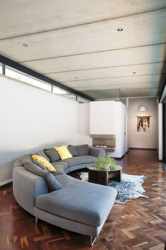 The link between the southern living area wing and northern bedroom wing also serves as the entrance, gallery and relaxation area. A wall with aribbon window at ceiling level faces the street onthe western side, and on the opposite side fold-away doors lead to the courtyard and pool.