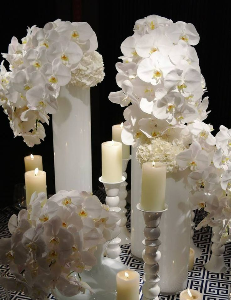 The welcome table will feature a cluster of white cylinder