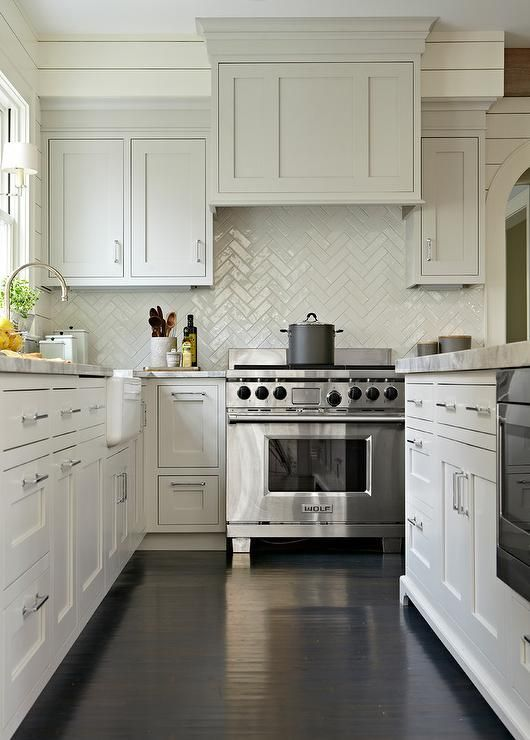 a white and gray kitchen boasts dark stained oak wood floors and ivory shiplap walls