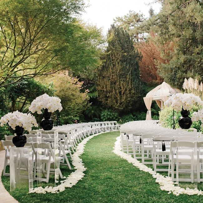 White petals and white chairs with black tassels added a modern, minimalist touch to the garden ceremony.