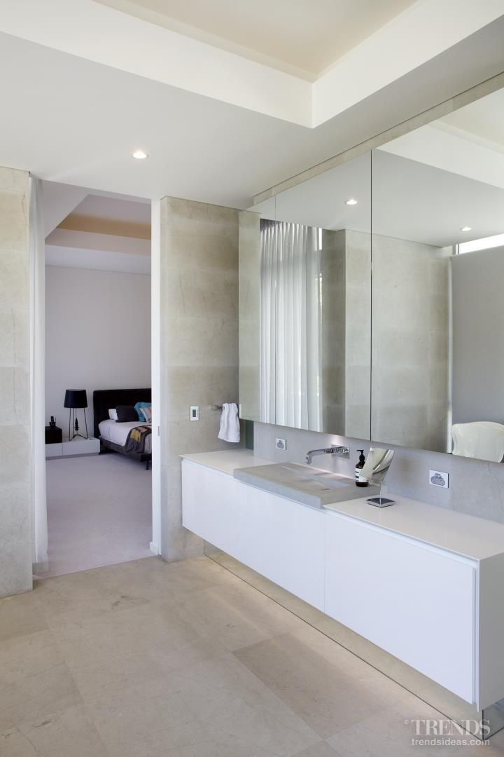 Modern master suite by architect Anthony Rechichi features wading basins, angular  freestanding bathtub, stone tiles