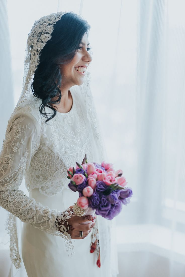 Bride holding her pink and purple floral bouquet dressed in lace veil and modest wedding dress // Andy and Hanis' wedding celebrations began with a Bollywood-themed henna night, and was followed by a traditional 'akad nikah' (or wedding solemnisation) and two receptions.