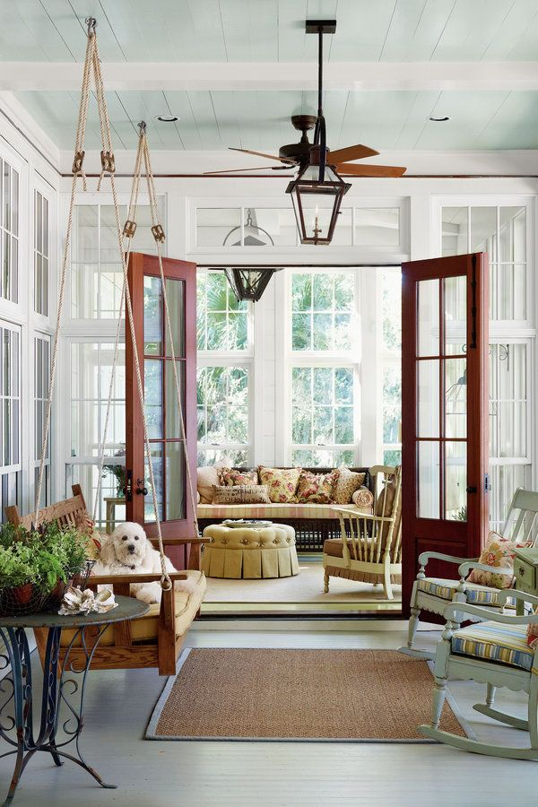 Floor-to-ceiling windows, a hanging porch swing, and bright fabrics create an outdoor feel for this enclosed space.  Tour the Daufuskie Island House