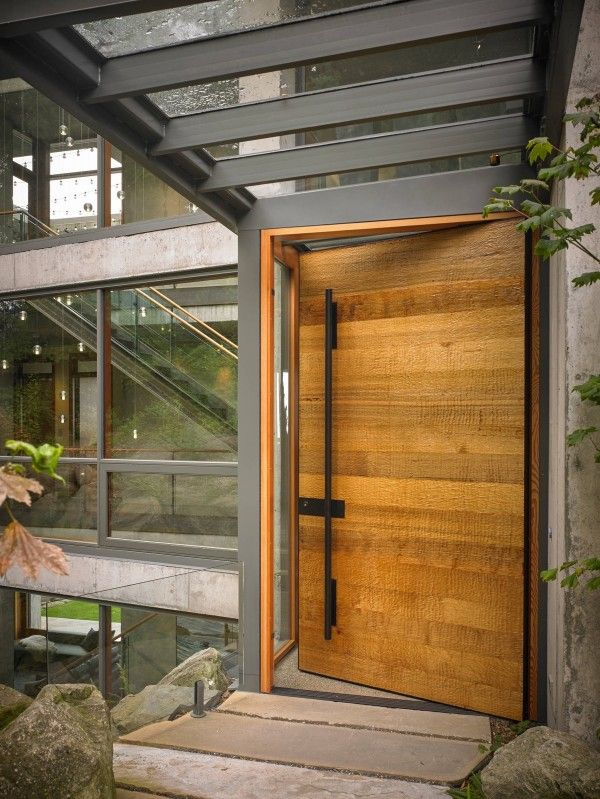 In the context of an industrial exterior like this one, a natural door can have an even bolder effect. This one has a textural exterior to stand in contrast with the concrete and steel that surrounds it.