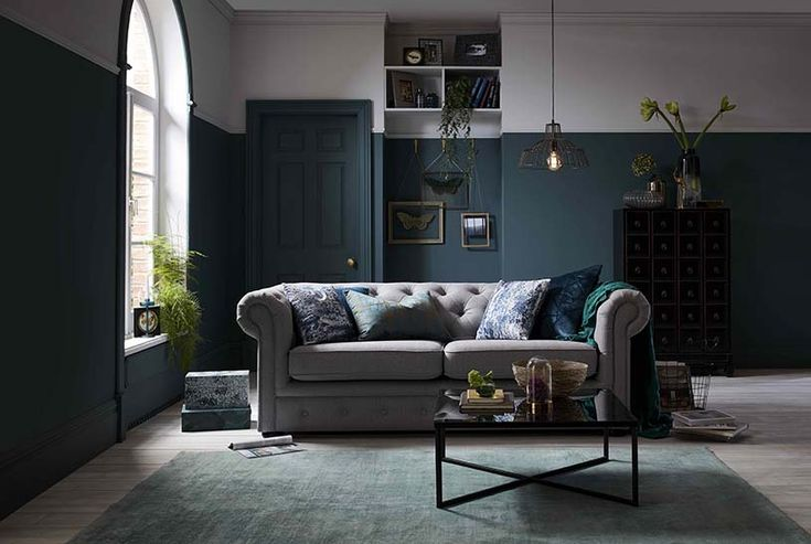 A beautiful grey sofa looks extra fine in this moody interior with dark green and grey color blocking on the walls. Image by DFS Furniture.