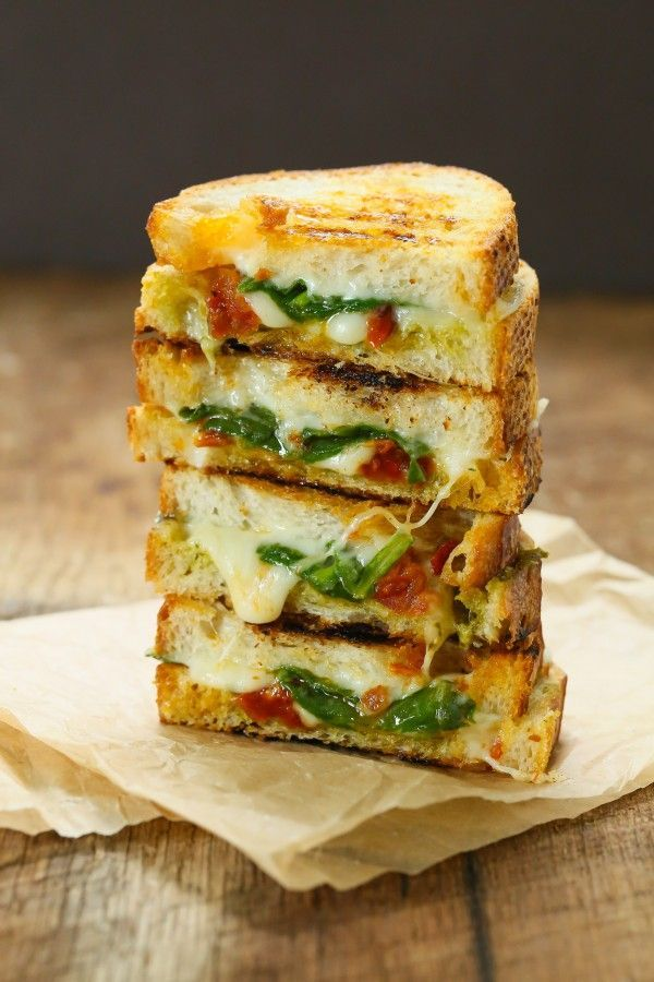 An amazing grilled cheese sandwich with sundried tomatoes, pesto and spinach.