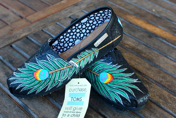 This pair of shoes feature a peacock feather on the outside of each shoe on these black glitter TOMS shoes. This price includes shoes+artwork For every pair of B Street TOMS ordered, a pair of shoes i
