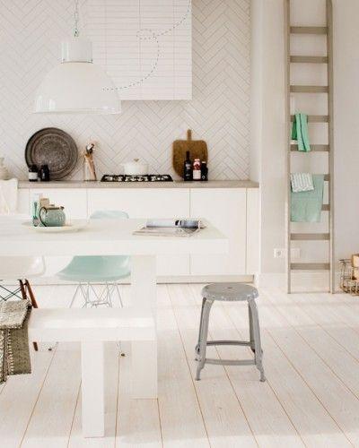 Cuisine blanche et touche pastel. Avec une crédence de céramiques joliment posées en chevron !