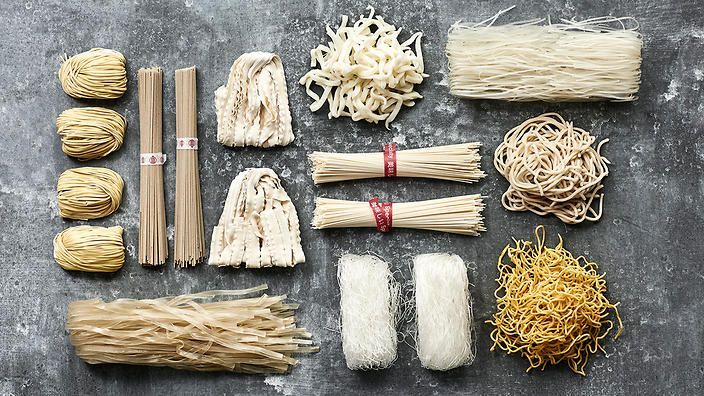 The huge variety includes (clockwose, from top left) dried egg noodles, buckwheat soba, knife-cut wheat noodles, fresh wheat noodles, mung bean noodles, fresh udon, fresh egg noodles, green bean thread noodles, sweet potato noodles and (centre) soba noodles.