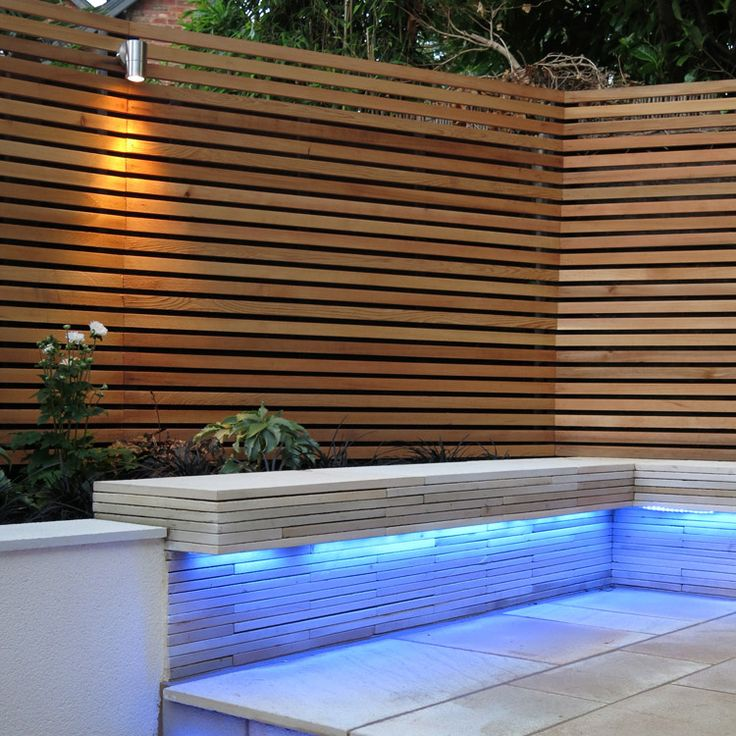 Beautiful Modern Contemporary Garden Fence using Western Red Cedar and downlighting. Great contrast with tiles and stonework. Garden designed by Blue Tulip Garden Design.