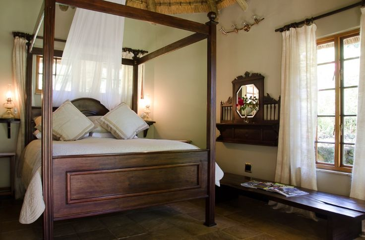 An African Elegance vibe was instilled in Wood Owl Cottage. Mohair cur- tains, wicker chairs and dark wood furniture create luxurious warmth and elegance along with the bespoke four poster bed.