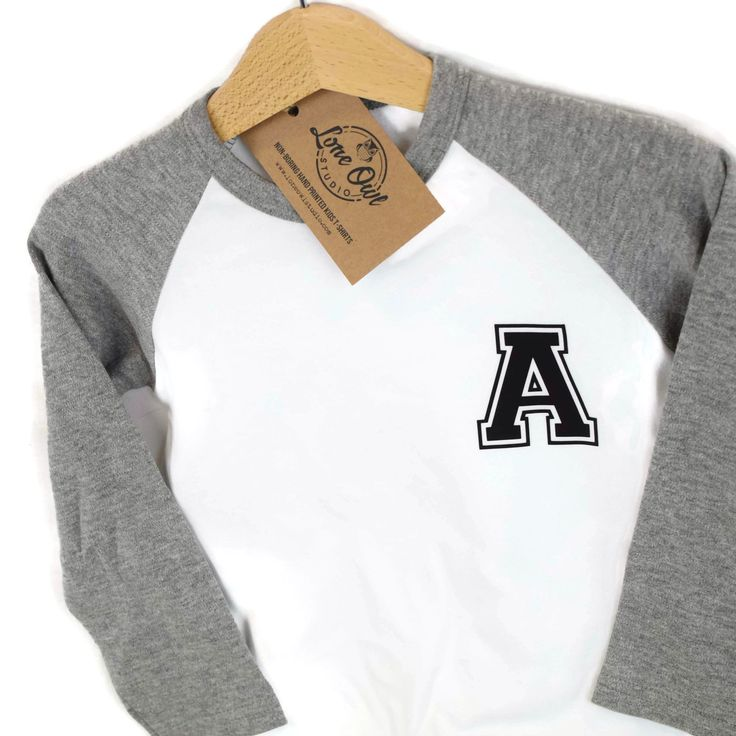 Baseball tops are here! This new design is a single letter on the left chest to personalise, in a cool, college style font.  Baseball tops are available with Grey or Black sleeves and in ages 6-12m up to 5-6 years. The fabric is SO soft and the long sleeves are perfect for this cold weather.