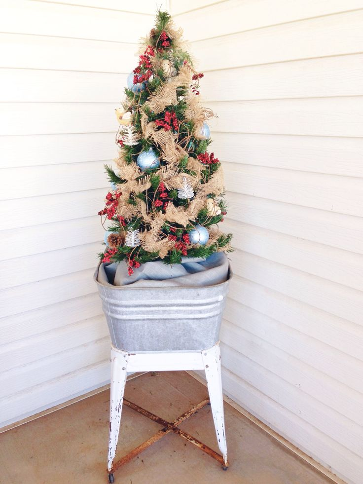 Christmas tree in a vintage galvanized wash tub, on a country porch. Decorated with burlap garland and grapevine.