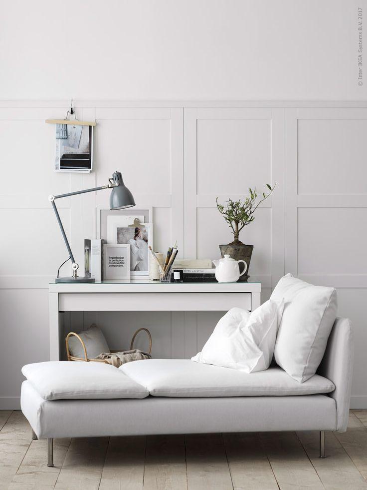 Smuk lys stue med daybed og konsolbord med billeder, lamper og en flot plante. Væggene er beklædt med høje skabslåger fra Ikea som gør det ud for høje paneler
