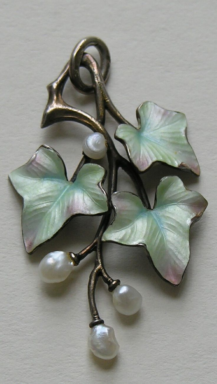Iridescent Enamel Leaves and Pearl Pendant  This lovely pendant is European in origin (most likely German) and features three enameled leaves with three freshwater pearl accents.  This pendant is very much in the style of Meyle and Mayer, a well know German firm (operating out of Pflorzheim) know for their lovely enamels.  The pendant measures 1 5/8ths inches by 1 inch and is marked 900 silver.