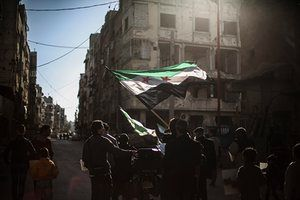 Syrians wave their national flag during a protest against the airstrikes in Douma, Syria