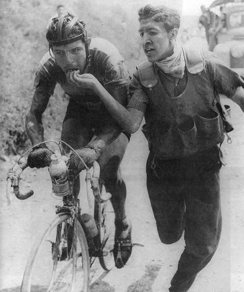 """Vuelta a Colombia 1959. Ricardo Ovalle es alimentado en la zona de avituallamiento. Inolvidable mirada fatigada del """"llanero solitario"""", quien corría aquí por primera vez una Vuelta a Colombia.  TITANESENDOSRUEDAS"""