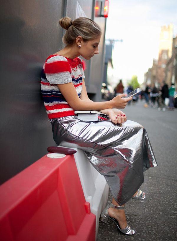 Foto de street style com blusa de tricot vermelha, saia metalizada prata