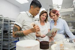 Pastry chefs with digital tablet in commercial kitchen