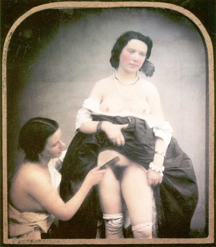 Una mujer semidesnuda peina el vello púbico de otra con la falda levantada y la blusa bajada. Daguerrotipo estereoscópico coloreado a mano. 1850.