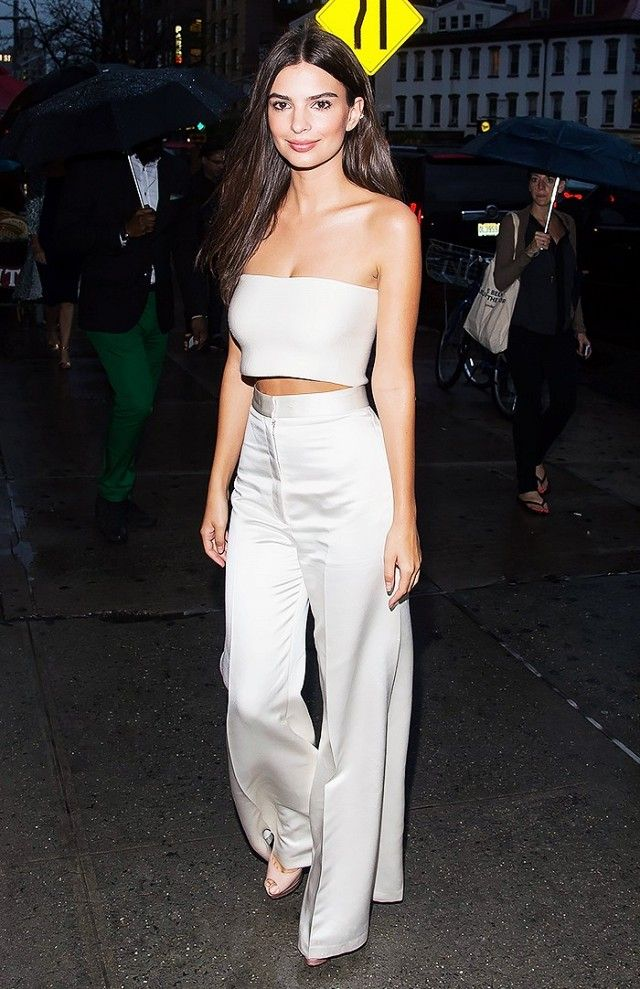 Emily Ratajkowski wears a chic crop top with high-waisted wide-leg trousers and peep-toe pumps