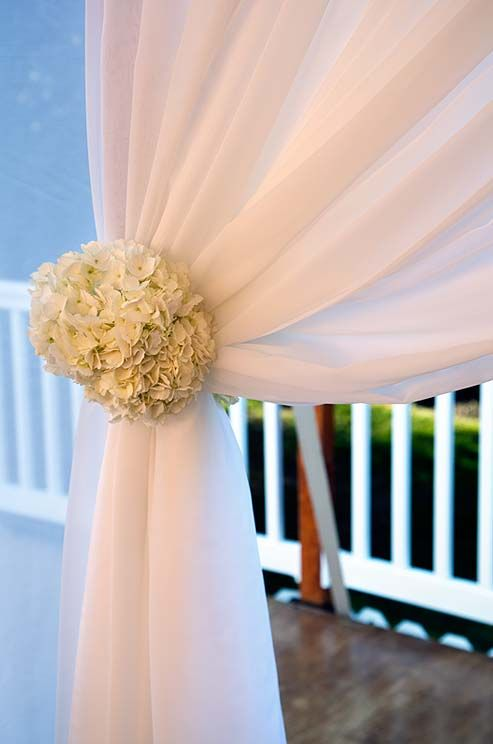 A cluster of hydrangeas accents this tent's sheer curtains.