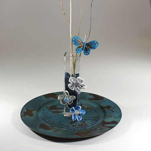 Nostalgisk dekoration i blåfarver. Den høje og smalle udformning på denne dekoration får den til at virke luftig og let, selvom der er brugt tunge farver. Dette skaber en fin balance i dekorationens helheld, og sørger for at den på trods af sit nostalgiske udtryk også virker moderne. Dekorationen anrettes på det blå plastfad i …