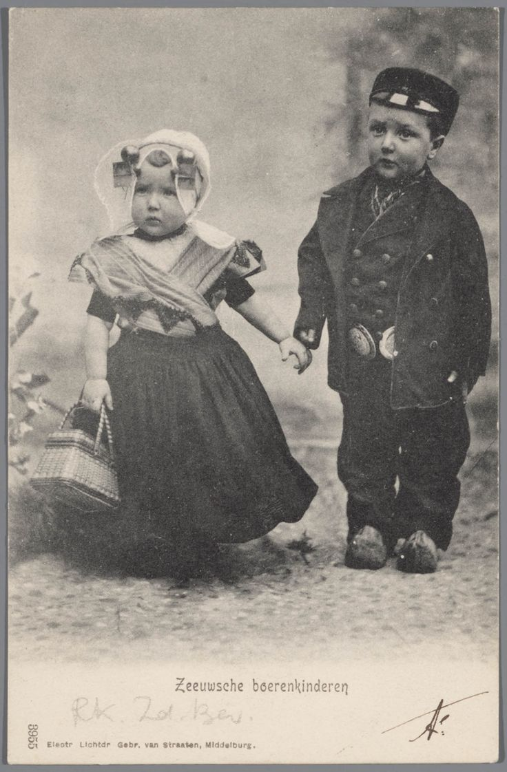 Jongen en meisje in katholieke Zuid-Bevelandse streekdracht. Het meisje draagt een oorijzer en ondermuts, met daarover de 'poepinnemuts' (meisjesmuts). Naast de uiteinden van het oorijzer zijn twee paar mutsenspelden in de ondermuts gestoken. De broek van de jongen wordt gesloten door zilveren 'klepstukken'. 1897-1905 #Zeeland #ZuidBeveland #katholiek