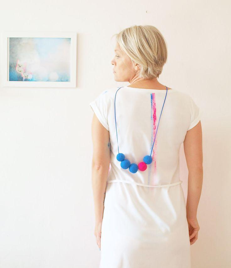 zdobení * Výrazné zdobení z větších plstěnek z jemného australského merina v zářivé růžové a jasné modré barvě.Navlečené na modré kůži o délce 115 cm.Kůže je barvou totožná s modrými plstěnkami.