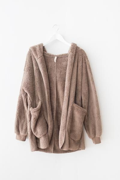 """Ultra soft and fuzzy faux fur """"teddy bear"""" style jacket. Oversized fit with large front patched pockets. Hooded with an open front. 100% Polyester Imported"""
